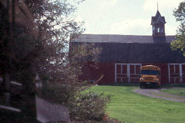 Barn with a school bus in front of it
